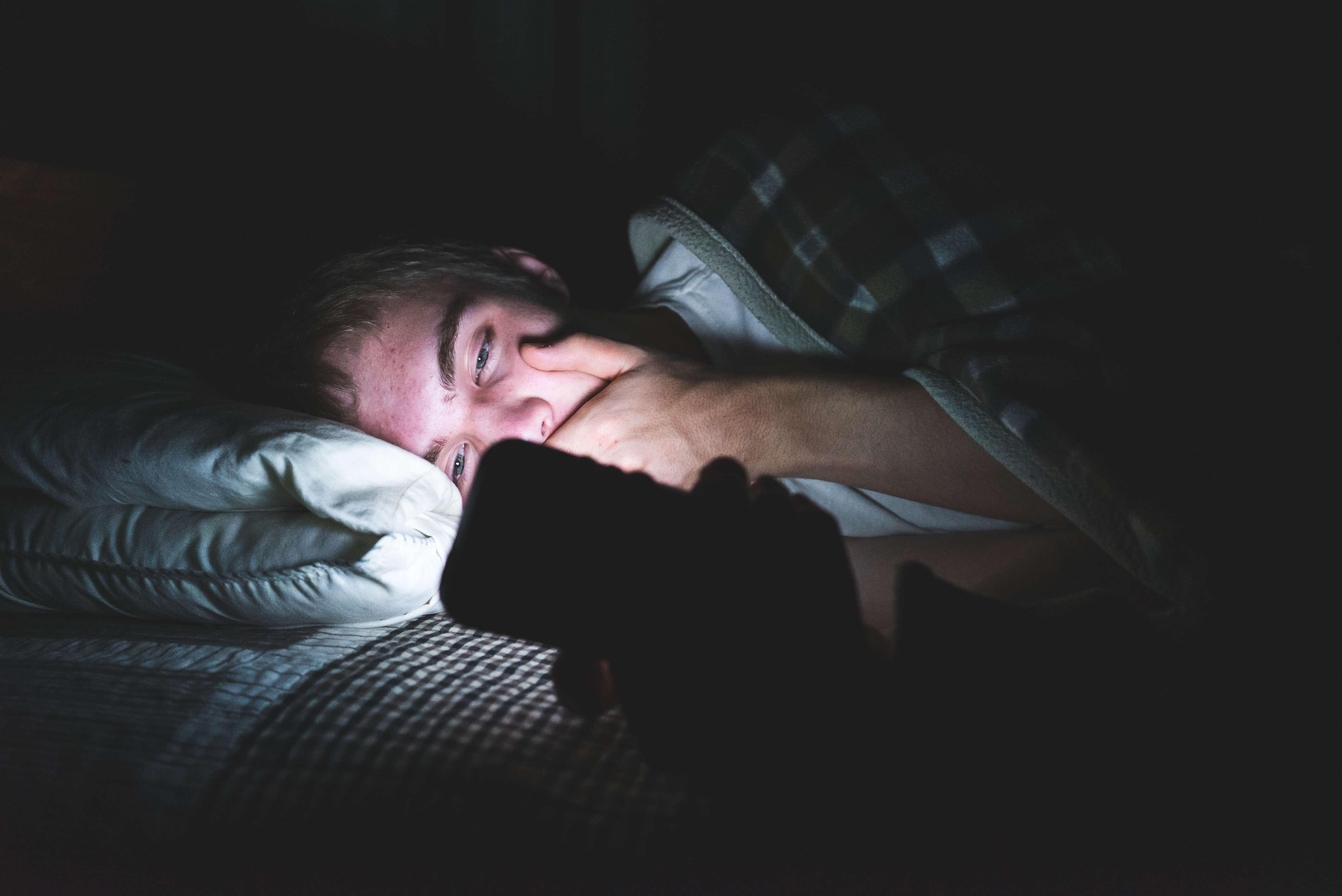 Mann mit Smartphone nachts im Bett
