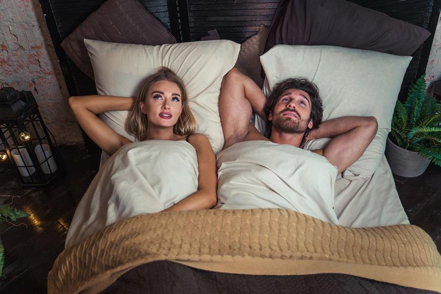 Paar liegt zusammen im Bett