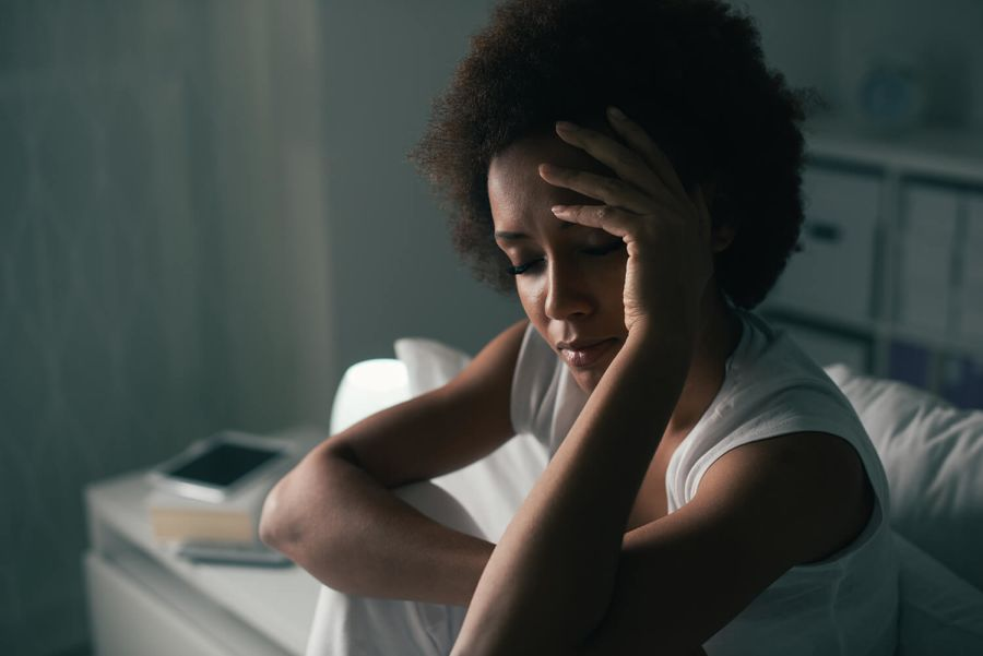 Frau sitzt deprimiert auf Bett